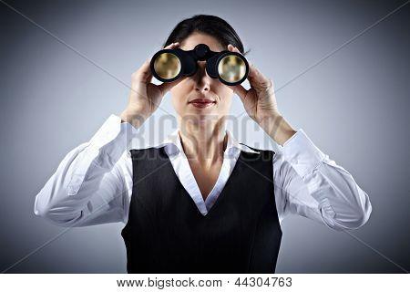Business-Frau mit dem Fernglas Ausspionieren von Konkurrenten.