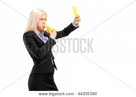 Young businesswoman blowing a whistle and showing a yellow card, isolated on white background
