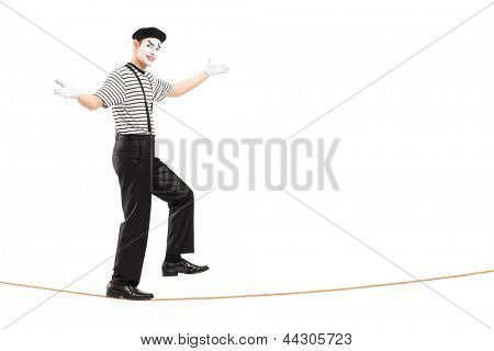 Full length portrait of a male mime artist walking on a rope, isolated on white background