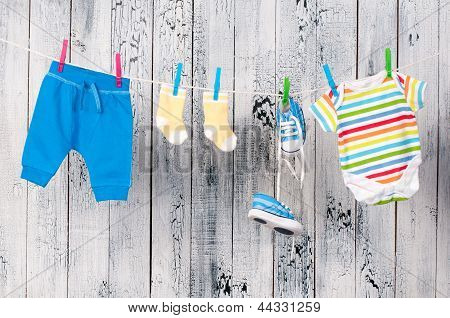 Baby clothes hanging on the clothesline. Taking care of the children. poster