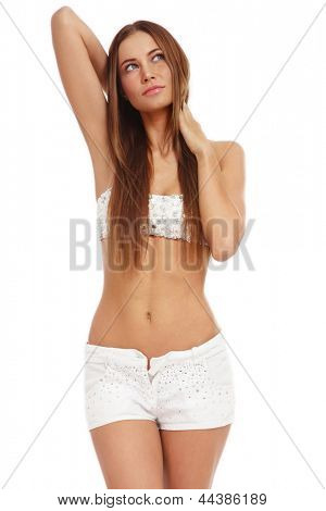 Beautiful slim tanned smiling girl in stylish swimsuit and shorts looking upwards, on white background