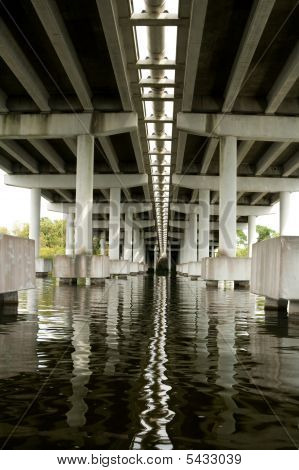 Underneath Concrete Bridge Looking At Supports And Reflection In Water