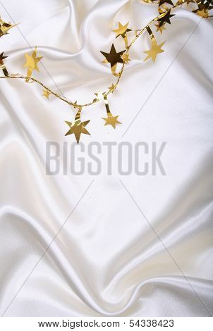 Golden stars and spangles on white silk as background poster