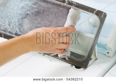 Horizontal photo of female hand taking the lent out from dirty air filter of the dyer machine poster