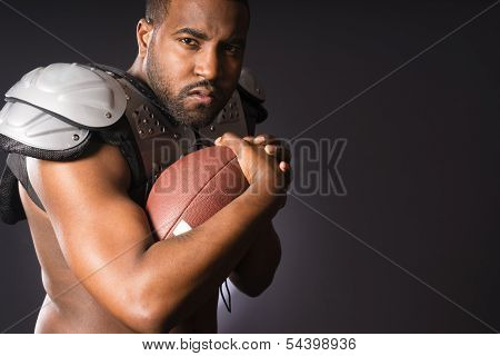 Angry African American Male Football Player Holds Ball Tight