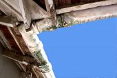 upward view of mouldy neglected asbestos guttering poster