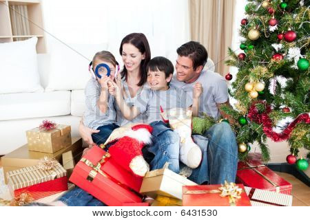 Happy family having fun with Christmas presents at home poster