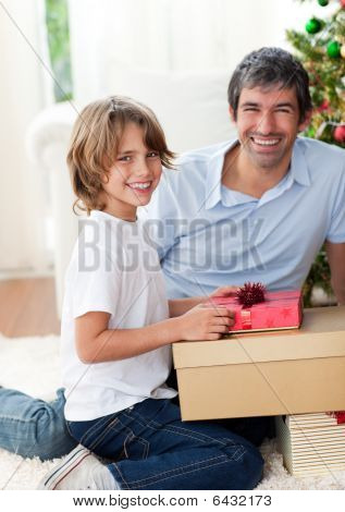 Smiling Father And His Son Opening Christmas Presents