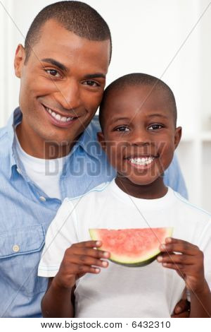 Portrait Of A Smiling Boy Eating Fruit With His Father
