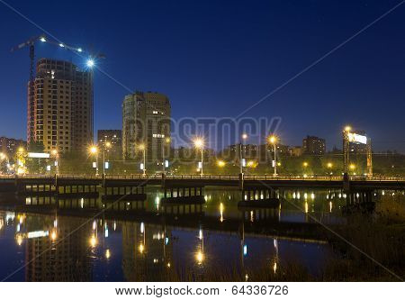 Night Scene With Illuminated Bridge Over River In Donetsk