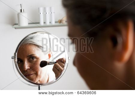 Happy senior woman making up