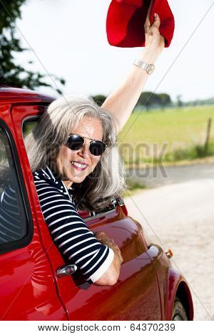Senior happy woman with vintage car