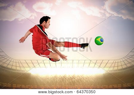 Football player in red kicking against large football stadium with spotlights under morning sky poster