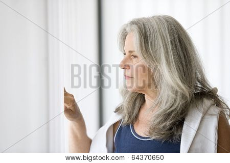 Portrait of senior woman looking outside the window