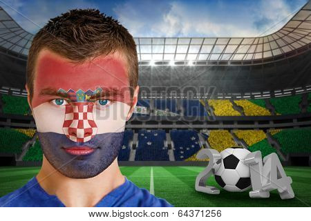 Composite image of serious young croatia fan with face paint against large football stadium poster