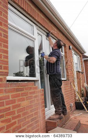 A Window fitter removing old windows and doors in preparation for new plastic ones to be fitted poster
