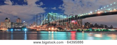 Brooklyn Bridge panorama over East River at night in New York City Manhattan with lights and reflections. poster