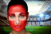 Composite image of beautiful swiss fan in face paint against vast football stadium with fans in white poster