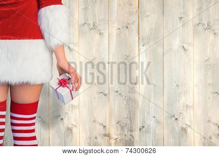 Pretty girl in santa outfit holding gift against pale wooden planks poster