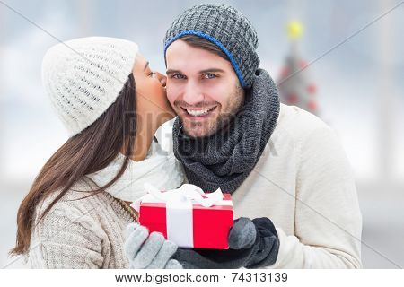 Winter couple holding gift against blurry christmas tree in room poster