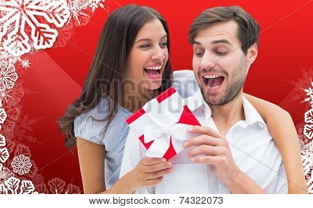Woman surprising boyfriend with gift against christmas themed snow flake frame poster