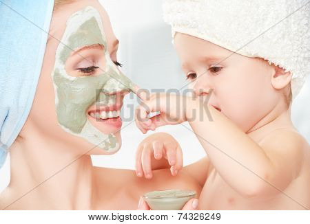 family beauty treatment in the bathroom. mother and daughter baby girl make a mask for a face skin poster