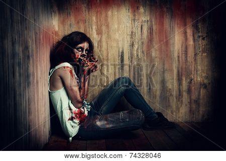 Terrible bloody zombie chews the bones of her victims. Halloween.