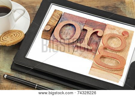 dot org internet domain for non-profit organization in letterpress wood type printing blocks on a digital tablet screen with a cup of coffee