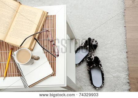 Still life details, cup of coffee, book and glasses on table, on home interior background