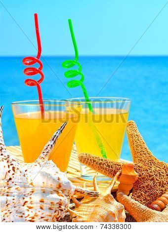 Fishstar, Shells And Two Glasses Of Orange Cocktail Against The Blue Sea