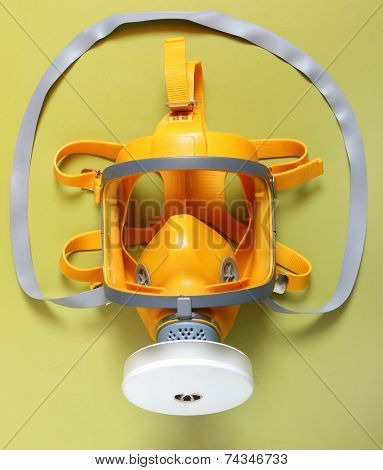 Yellow gas mask - respirator on a green background.
