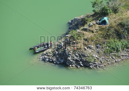 UVAC RIVER, SERBIA - AUGUST 12, 2014: aerial view of a fisherman and his rubber dinghy and his bivouac in the Uvac Special Nature Reserve near Sjenica in Serbia.
