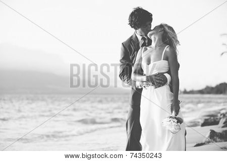 Beautiful Wedding Couple, Bride and Groom Kissing on the Beach at Sunset. Black and White Photograph