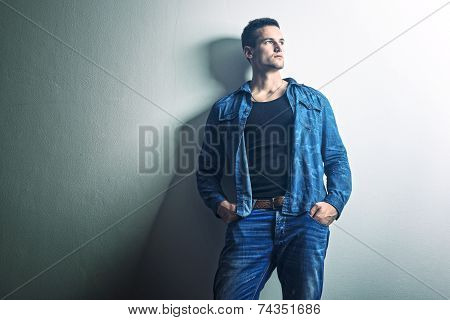 Handsome man - full jeans thinking relies on the Wall
