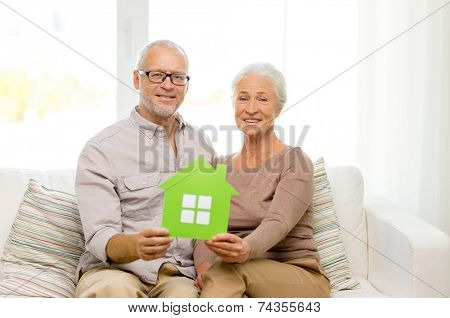 family, relations, real estate, age and people concept - happy senior couple with green paper house cutout at home