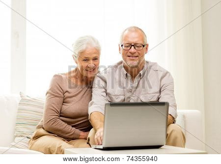 family, technology, age and people concept - happy senior couple with laptop computer at home