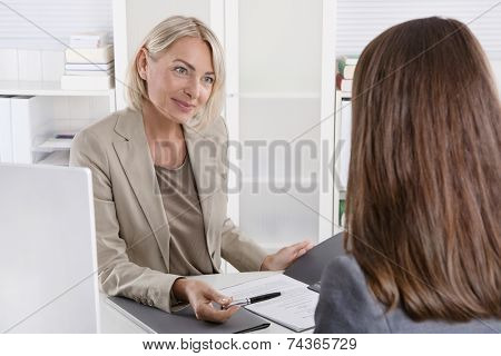 Female managing director in a job interview with a young woman.