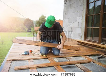 Handyman installing wooden flooring in patio outside the new house poster
