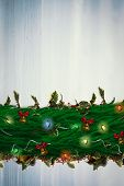 Fir branch christmas decoration garland against bleached wooden planks background poster