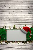 Fir branch christmas decoration garland against digitally generated grey wooden planks poster