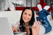 Woman ordering shopping from online against blurry christmas tree in room poster