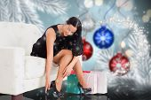 Woman sitting with shopping bags against baubles hanging over christmas scene poster