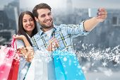 Happy couple taking a selfie against room with large window looking on city poster