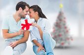 Young couple holding gift against blurry christmas tree in room poster