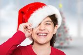 Festive little girl smiling at camera against blurry christmas tree in room poster