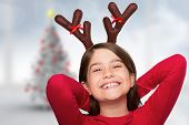 Festive little girl wearing antlers against blurry christmas tree in room poster