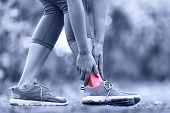 Broken twisted ankle - running sport injury. Female runner touching foot in pain due to sprained ankle. poster