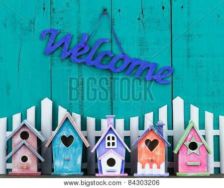 Welcome sign hanging over fence and birdhouses