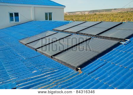 Solar water heating system on the house roof. poster