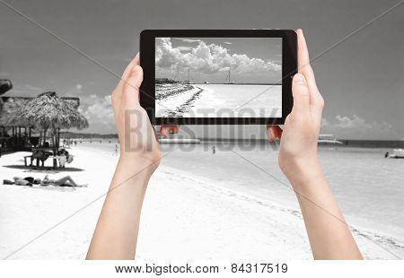 travel concept - tourist taking photo of Atlantic Ocean coastline in Varadero on mobile gadget Cuba poster